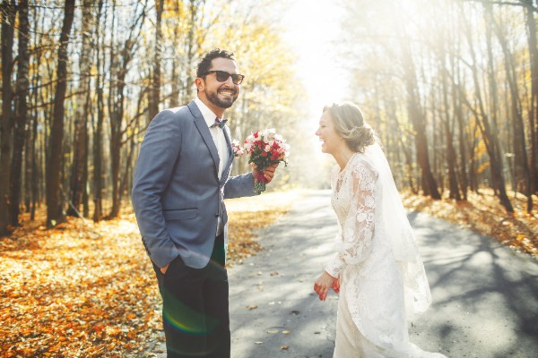 Smiling wedding couple in love on road covered with leaves