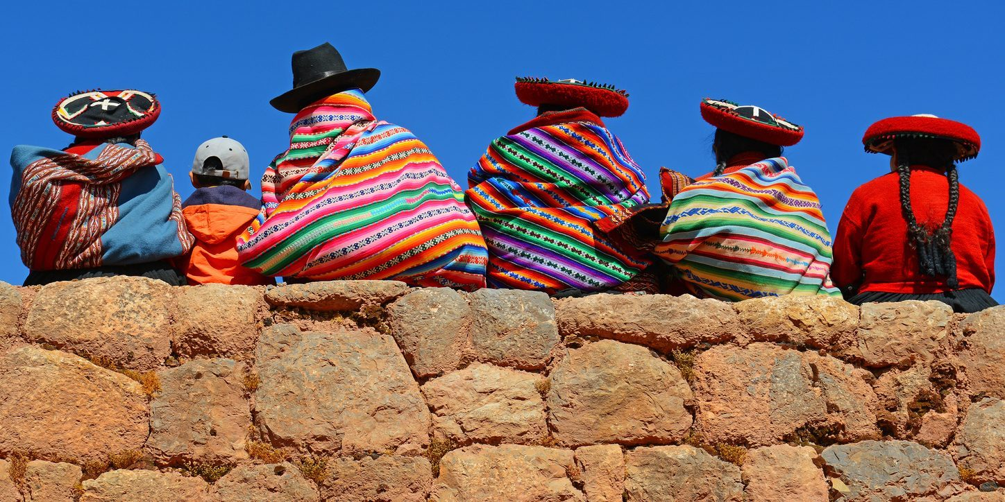 Quechua ladies with colorful textiles and hats sitting on an ancient Inca Wall together with a young boy with modern clothing.